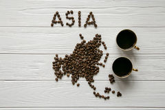 Map of the Asia made of roasted coffee beans laying on white wooden textured background with two cups of coffee. Map of the Asia made of roasted coffee beans Royalty Free Stock Photography