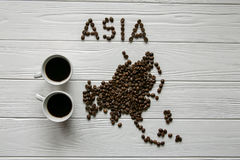 Map of the Asia made of roasted coffee beans laying on white wooden textured background with two cups of coffee. Map of the Asia made of roasted coffee beans Royalty Free Stock Photo
