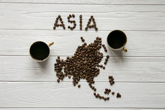 Map of the Asia made of roasted coffee beans laying on white wooden textured background with two cups of coffee Royalty Free Stock Image