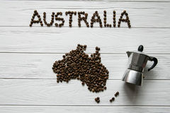 Map of the Australia made of roasted coffee beans laying on white wooden textured background with coffee maker. Space for text Stock Images
