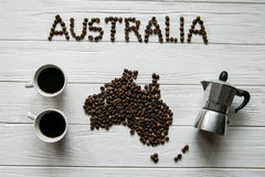 Map of the Australia made of roasted coffee beans laying on white wooden textured background with coffee maker and two coffee cups. Space for text Stock Photography