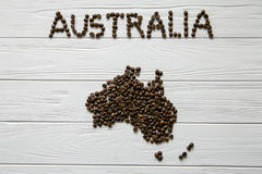 Map of the Australia made of roasted coffee beans laying on white wooden textured background Royalty Free Stock Photography