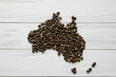 Map of the Australia made of roasted coffee beans laying on white wooden textured background Royalty Free Stock Image