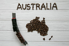 Map of the Australia made of roasted coffee beans laying on white wooden textured background with toy train. Space for text Stock Photos