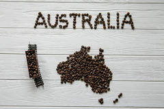 Map of the Australia made of roasted coffee beans laying on white wooden textured background with toy train. Space for text Royalty Free Stock Image