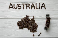Map of the Australia made of roasted coffee beans laying on white wooden textured background with toy train. Space for text Royalty Free Stock Photo