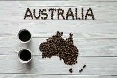 Map of the Australia made of roasted coffee beans laying on white wooden textured background with two coffee cups. Space for text Royalty Free Stock Photography