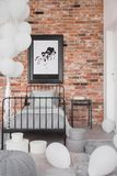 Map in black frame on brick wall in classy bedroom interior with industrial single bed with grey bedding and bunch of white. Balloons stock photo