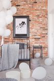 Map in black frame on brick wall in fashionable bedroom interior with industrial single bed with grey bedding and bunch of white. Balloons in the corner royalty free stock image