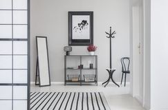 Map in black frame on the grey wall of corridor with mirror, shelf, hanger and hair. Real photo royalty free stock photo
