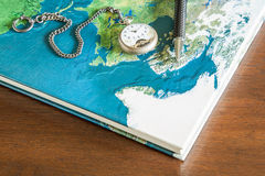Map book, pens, pocket watch. On wood table Royalty Free Stock Photo
