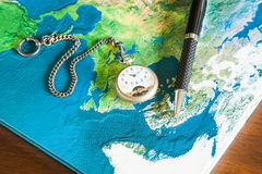 Map book, pens, pocket watch. On wood table Royalty Free Stock Photos
