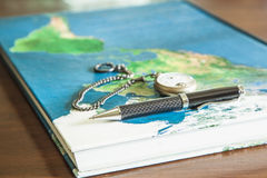 Map book, pens, pocket watch. On wood table Stock Photography