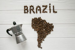 Map of the Brazil made of roasted coffee beans laying on white wooden textured background with coffee maker. Map of the Brazil made of roasted coffee beans Royalty Free Stock Photography