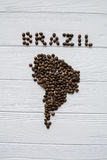 Map of the Brazil made of roasted coffee beans laying on white wooden textured background. Space for text Royalty Free Stock Photo