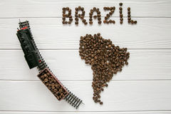 Map of the Brazil made of roasted coffee beans laying on white wooden textured background with toy train. Space for text Royalty Free Stock Photos