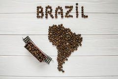 Map of the Brazil made of roasted coffee beans laying on white wooden textured background with toy train. Map of the Brazil made of roasted coffee beans laying Royalty Free Stock Photo