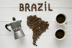 Map of the Brazil made of roasted coffee beans laying on white wooden textured background with two coffe cups and coffee maker. Map of the Brazil made of roasted Stock Photo