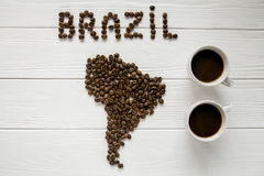 Map of the Brazil made of roasted coffee beans laying on white wooden textured background two cups of coffee. Map of the Brazil made of roasted coffee beans Royalty Free Stock Photos