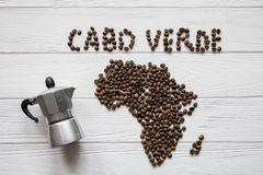 Map of the Cabo Verde made of roasted coffee beans laying on white wooden textured background with coffee maker. And space for text Stock Photos
