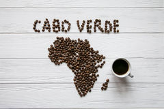 Map of the Cabo Verde made of roasted coffee beans laying on white wooden textured background with cup of coffee. And space for text Stock Photo