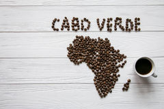 Map of the Cabo Verde made of roasted coffee beans laying on white wooden textured background with cup of coffee. And space for text Stock Photography