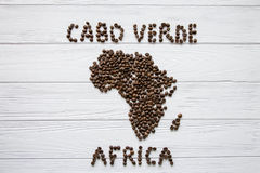 Map of the Cabo Verde made of roasted coffee beans laying on white wooden textured background. And space for text Royalty Free Stock Photos