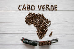 Map of the Cabo Verde made of roasted coffee beans laying on white wooden textured background with toy train. And space for text Royalty Free Stock Photo