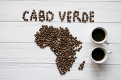 Map of the Cabo Verde made of roasted coffee beans laying on white wooden textured background with two cups of coffee. And space for text Royalty Free Stock Images