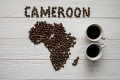 Map of the Cameroon made of roasted coffee beans layin on white wooden textured background with two coffee cups. And space for text Royalty Free Stock Photo