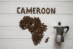 Map of the Cameroon made of roasted coffee beans laying on white wooden textured background with coffee maker. And space for text Stock Photo