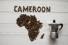 Map of the Cameroon made of roasted coffee beans laying on white wooden textured background with coffee maker. And space for text Stock Photos