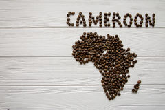 Map of the Cameroon made of roasted coffee beans laying on white wooden textured background. Space for text Royalty Free Stock Images