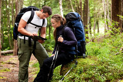 Map Camping. A couple of backpackers looking at a map in the forest Stock Photos