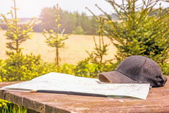 Map and cap. On wooden table Stock Photos