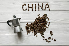 Map of the China made of roasted coffee beans laying on white wooden textured background  with coffee maker Royalty Free Stock Photos