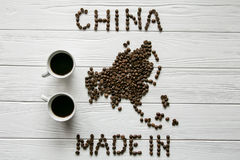 Map of the China made of roasted coffee beans laying on white wooden textured background cups of coffee. Map of the China made of roasted coffee beans laying on Royalty Free Stock Photo