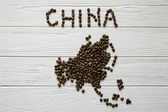 Map of the China made of roasted coffee beans laying on white wooden textured background. Space for text Stock Images