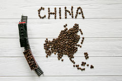 Map of the China made of roasted coffee beans laying on white wooden textured background with toy train. Space for text Royalty Free Stock Photography