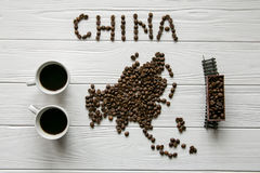 Map of the China made of roasted coffee beans laying on white wooden textured background with toy train and two cups of coffee. Space for text Royalty Free Stock Photos