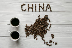 Map of the China made of roasted coffee beans laying on white wooden textured background  with two cups of coffee Stock Photos