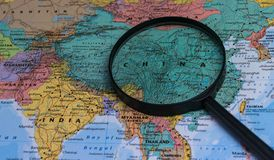 Map of china through magnifying glass on a world map. Map of china through magnifying glass on a world map Royalty Free Stock Photos