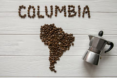 Map of the Columbia made of roasted coffee beans laying on white wooden textured background with coffee maker. Map of the Columbia made of roasted coffee beans Royalty Free Stock Images