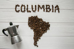 Map of the Columbia made of roasted coffee beans laying on white wooden textured background with coffee maker. Map of the Columbia made of roasted coffee beans Stock Image