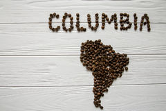 Map of the Columbia made of roasted coffee beans laying on white wooden textured background. Space for text Stock Images