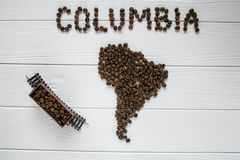 Map of the Columbia made of roasted coffee beans laying on white wooden textured background toy train. Map of the Columbia made of roasted coffee beans laying on Stock Photo