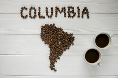 Map of the Columbia made of roasted coffee beans laying on white wooden textured background with two coffee cups. Map of the Columbia made of roasted coffee Royalty Free Stock Photo