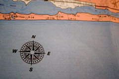Map with compass. Closeup of an old map with compass icon in the lower left corner Royalty Free Stock Images