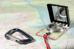 Map and Compass. A compass and carabiner sit atop a topographic map Royalty Free Stock Images