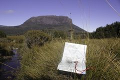 A map and a compass on a buttongrass plain in front of a rocky escarpment on Tasmania Australia`s Overland Track. In autumn under a clear blue sky stock photography